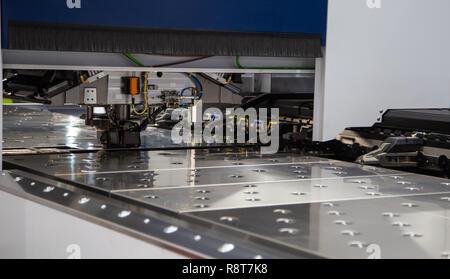 Laser cutting machine cutting metal sheet in industrial factory - Stock Photo