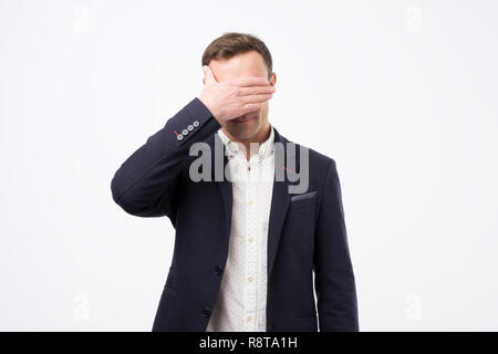 Manager in suit covering his face with hand. Negative news at work. Man is totally upset and stressed. - Stock Photo