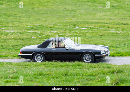 Black 1988 Jaguar XJ-S V12 convertible classic sports car driving along country road through meadow - Stock Photo