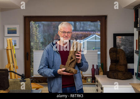 Saterland, Germany. 22nd Nov, 2018. Karl-Heinz Brinkmann holds the figure 'The Dancer' carved from peat in his hands in his home workshop. The 64 year old Saterland artist works with many materials. But the dried white peat is special: it is 2000 years old. Credit: Mohssen Assanimoghaddam/dpa/Alamy Live News - Stock Photo