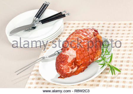 Roll of smoked ham on plate. Decorated with rosemary. The bread is on backgroud. Selective focus. - Stock Photo