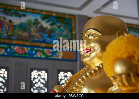 Detail of Gilt Smiling Fat Buddha inside Kuang Im Chapel, near River Kwai, Kanchanaburi, Thailand. - Stock Photo