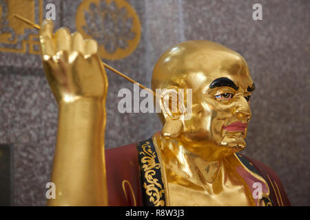 Detail of Gilt Lohan Arhat cleaning his ears with stick inside Kuang Im Chapel, near River Kwai, Kanchanaburi, Thailand. - Stock Photo