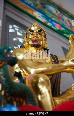 Detail of Gilt Lohan Arhat taming a dragon, inside Kuang Im Chapel, near River Kwai, Kanchanaburi, Thailand. - Stock Photo