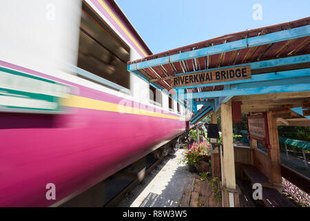 Motion-blurred train whizzes past old waiting gazibo of the Siam-Burma Railway over River Kwai in Kanchanaburi, Thailand. The infamous River Kwai brid - Stock Photo
