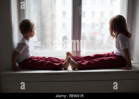 the little boy and girl alone at home watching in the window - Stock Photo