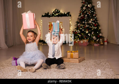 the little boy and girl open Christmas presents Christmas tree new year's Eve family celebration - Stock Photo
