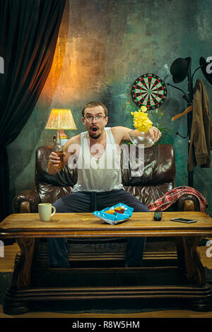 The crazy football fan watching soccer game on television on sofa couch at home with beer and looking anxious and scared of loosing. The nervous, excited, suffering, stress, emotions concept - Stock Photo