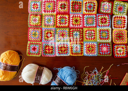 Balls of wool for a brightly pastel coloured granny square woollen baby blanket, traditional hand made crochet home handicraft and cut threads - Stock Photo