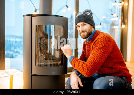 Portrait of a handsome man in sweater near the fireplace in the modern house during the winter time - Stock Photo