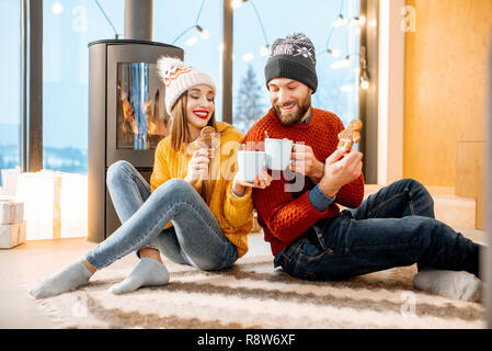 Young couple dressed in bright sweaters sitting together with hot drinks near the fireplace in the modern house in the mountains durnig winter time - Stock Photo