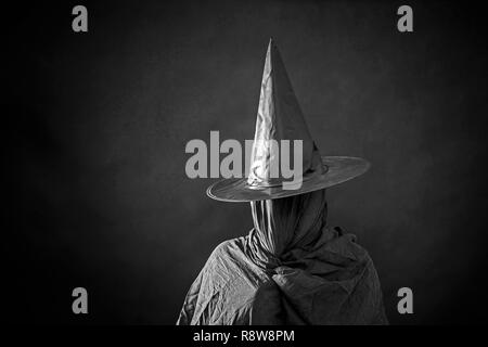 Ghostly figure with long hat in the dark - Stock Photo