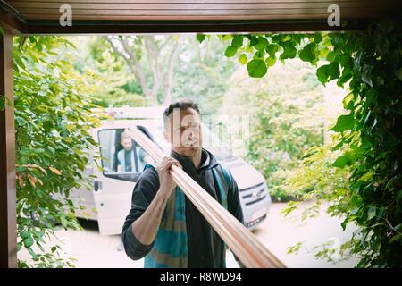 Portrait confident carpenter carrying equipment in garage - Stock Photo
