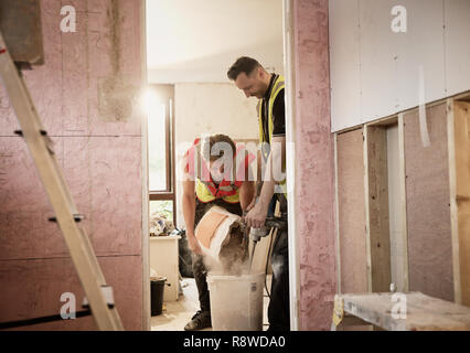 Construction workers mixing plaster in house - Stock Photo