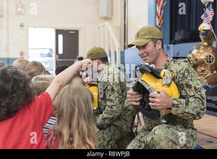 U.S. Navy Diver 1st Class Jason Thurston, assigned to Mobile Diving and Salvage Unit (MDSU) 2, talks about the KM-37 diving helmet to kindergarten students during a community outreach event at Central Elementary School in Maple, N.C., March 8, 2017. - Stock Photo