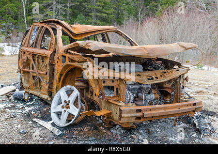 Burnt down rusty vehicle abandoned in the woods with its body falling off due to fire damage and nature forces. - Stock Photo
