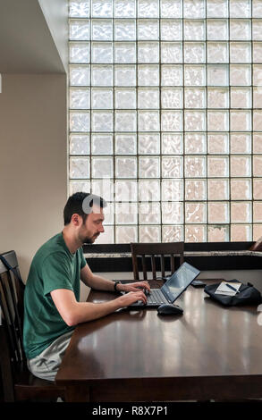 Young bearded man at home working remotely on laptop computer in front of glass block wall - Stock Photo