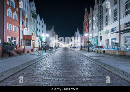 Old town of Elblag, Poland at night. Renovated tenement houses on Stary Rynek street with medieval Market Gate (polish: Brama Targowa). - Stock Photo