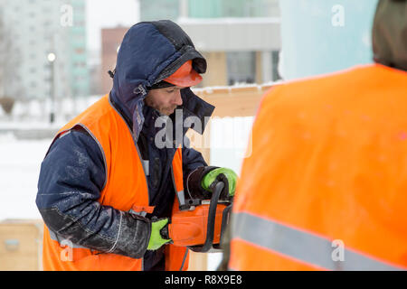 Work installer in a protective helmet and reflective vest with a chainsaw in profile - Stock Photo