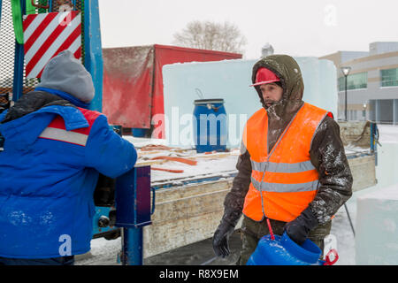 Portrait of an assembler worker in a hooded jacket who holds in his hand a blue barrel - Stock Photo