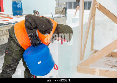 Portrait of an assembler worker in a hooded jacket that pours snow out of a blue barrel - Stock Photo