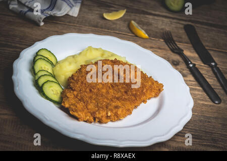 Chicken fried schnitzel with mashed potatoes and lemon on wood table - Stock Photo