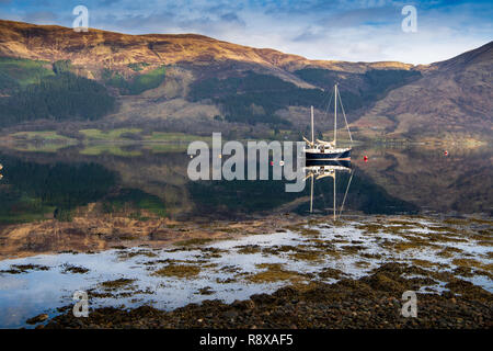 Blue sailboat reflected in the waters of Loch Leven, Scotland. - Stock Photo