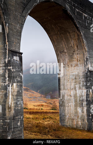 White stone cottage nestled in the Scottish highlands framed by a viaduct archway. - Stock Photo