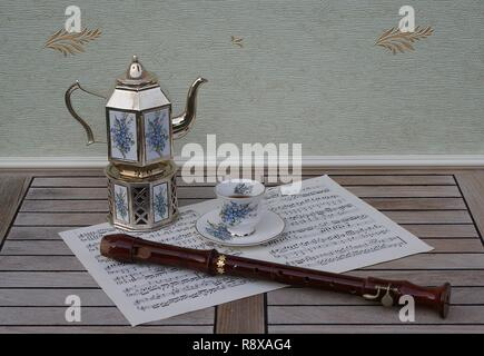 English teacup and saucer, silver-plated teapot on a silver stove, with floral decor and a block flute on a sheet of music - Stock Photo