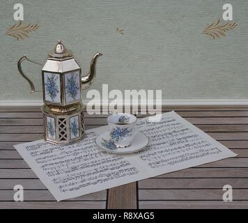 English teacup and saucer, silver-plated teapot on a silver stove, with floral decor, on a sheet of music - Stock Photo