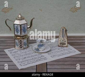 English teacup and saucer, silver-plated teapot on a silver stove, with floral decor and metronome for music on a sheet of music - Stock Photo