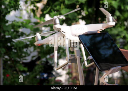 Man is holding a drone in hand and using of new technology. White quad copter Drone and photographer man hands. Professional drone pilot holds panel. - Stock Photo