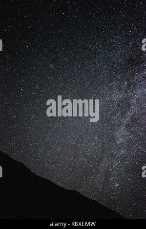 night sky full of stars over mountains, shooting star and milky way - Stock Photo