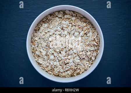 Dry rolled oatmeal in bowl isolated on dark background. Scattered oat flakes. - Stock Photo