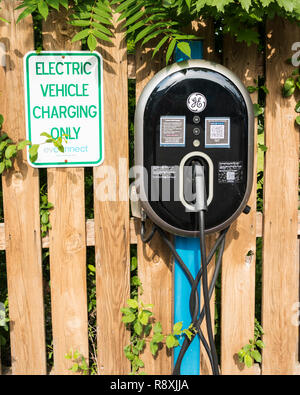 Syracuse, NY, USA - 8 June 2018: A free electric car charging station provided by GE in a hotel parking lot for their guests to use. - Stock Photo