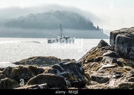 A lobster boat heading out of Bar Harbor Maine with porcupine island covered in fog in the background on an August morning. - Stock Photo