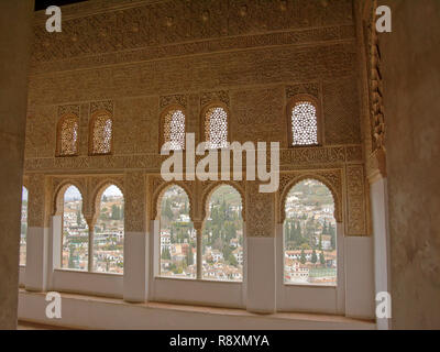 Heavily decorated wall with horseshoe shaped windows looking onto Albayzin neighbrhood, Nasrid Palace , Alhambra, Spain - Stock Photo