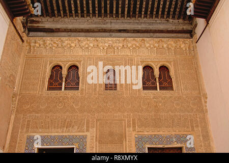 Wall with elaborate organic decorative patterns and caligraphy and windows with stars and other shapes, detail of Nasrid Palace , Alhambra, Spain - Stock Photo