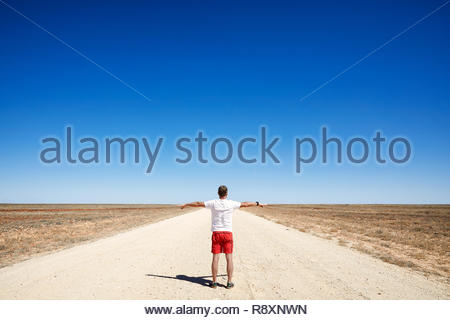 Rear view of man on road looking toward horizon in outback Australia - Stock Photo