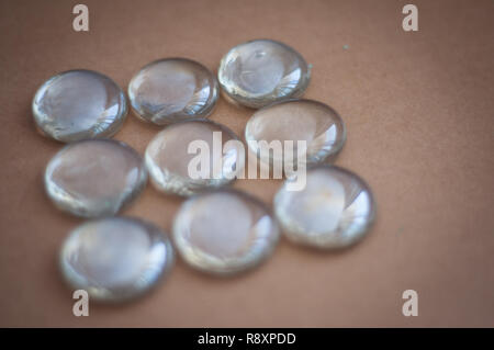 Clear marbles with light reflections on a brown background. - Stock Photo