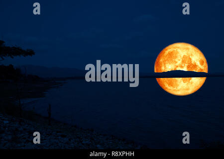 full blood moon back on mountain and reflection on lake ,Elements of this image furnished by NASA - Stock Photo