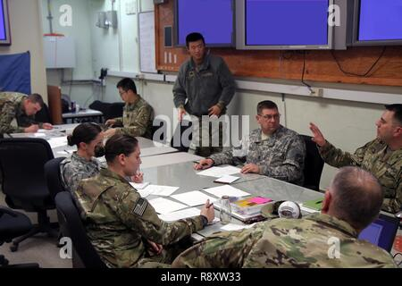 Soldiers from the 129th Mobile Public Affairs Detachment, South Dakota Army National Guard, and Eighth Army discuss media center operations during the Key Resolve training exercise at U.S. Army Garrison Daegu, South Korea, March 15, 2017. Key Resolve is a multinational training exercise that enhances U.S. and ROK forces' operational capabilities to increase alliance readiness, protect the region and maintain stability on the Korean Peninsula. - Stock Photo