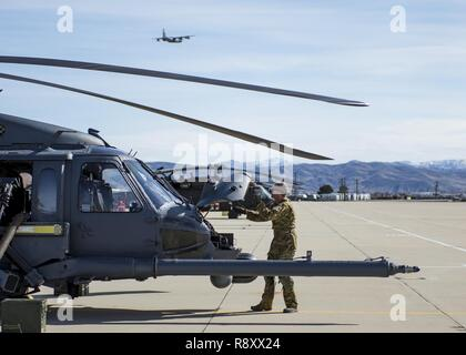An Airman with the 943rd Rescue Group performs a pre-flight inspection on an HH-60G Pave Hawk helicopter as HC-130J Combat King II flies over head, March 3, 2017, at Gowen Field, Idaho, during pre-deployment training for the 305th Rescue Squadron. The 305th RQS, located at Davis-Monthan Air Force Base, Ariz., is conducting training at the Idaho Air National Guard's Orchard Combat Training Center, a 143,000-acre live-fire range located south of Boise, Idaho, to hone all of their search and rescue procedures before heading to Southwest Asia. - Stock Photo