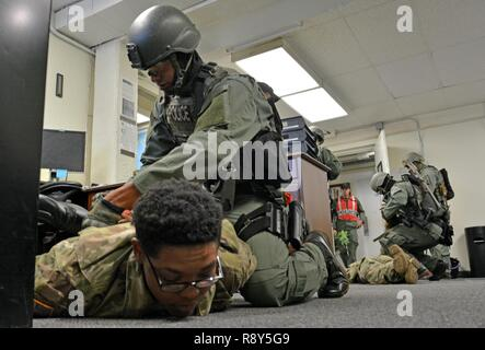 FORT SHAFTER, Hawaii- Members of the Special Reaction Team (SRT), 39th Military Police Detachment, 728th MP Battalion, 8th MP Brigade, 8th Theater Sustainment Command, secure two Soldiers with hand restraints during an active shooter training exercise Feb. 23, here. - Stock Photo
