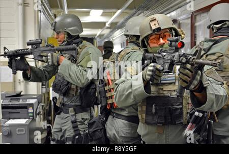 FORT SHAFTER, Hawaii- Members of the Special Reaction Team (SRT), 39th Military Police Detachment, 728th MP Battalion, 8th MP Brigade, 8th Theater Sustainment Command, secure a hallway during an active shooter training exercise Feb. 23, here. - Stock Photo