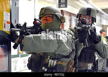 FORT SHAFTER, Hawaii- Members of the Special Reaction Team (SRT), 39th Military Police Detachment, 728th MP Battalion, 8th MP Brigade, 8th Theater Sustainment Command, secure a hallway while fellow teammates clear rooms during an active shooter training exercise Feb. 23, here. - Stock Photo