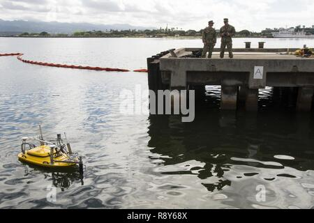 Navy underwater construction team members demonstrate the capabilities of a Multifunctional Assessment Reconnaissance Vehicle (MARV) to capture detailed engineering survey data.  Army and Navy divers assigned to engineer units partnered for a technology demonstration at Pearl Harbor Victor Pier 3, March 3, 2017. The MARV is a remote operated vehicle equipped with sensors and cameras, used for collecting data to identify damaged areas beneath the pier. - Stock Photo