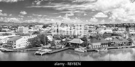 St johns, Antigua - March 05, 2016: city and sea port on cloudy blue sky. Summer vacation on tropical island. Travelling and wanderlust. - Stock Photo