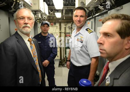 Coast Guard Lt. Cmdr. Joe Rizzo, cutter Lawrence Lawson commanding officer, and Chief Petty Officer David Quigley, ship's engineering petty officer, provide a tour of the cutter's engine room to Reps. Dan Newhouse and Chuck Fleischmann, while in Washington, D.C., Thursday, Mar. 9, 2017. The U.S. Representatives had an opportunity to tour the newest ship in the Coast Guard fleet prior to its Mar. 18, 2017 commissioning in Cape May, N.J. U.S. Coast Guard - Stock Photo