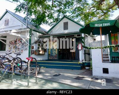 Shady sidewalk view of classic Key West, Florida buildings at Green Parrot Bar on Whitehead Street, with mural tribute to Robert Johnson. - Stock Photo